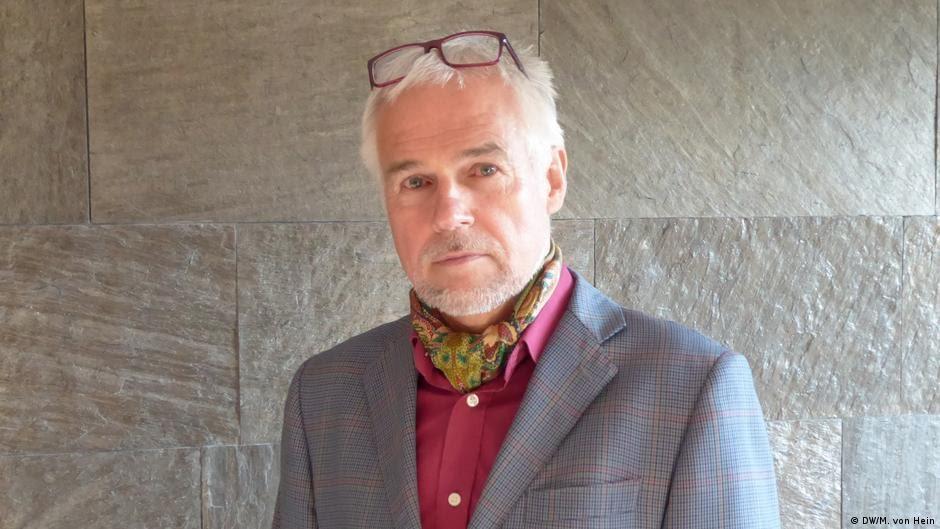 Matthias von Hein wearing a red shirt and blue jacket.